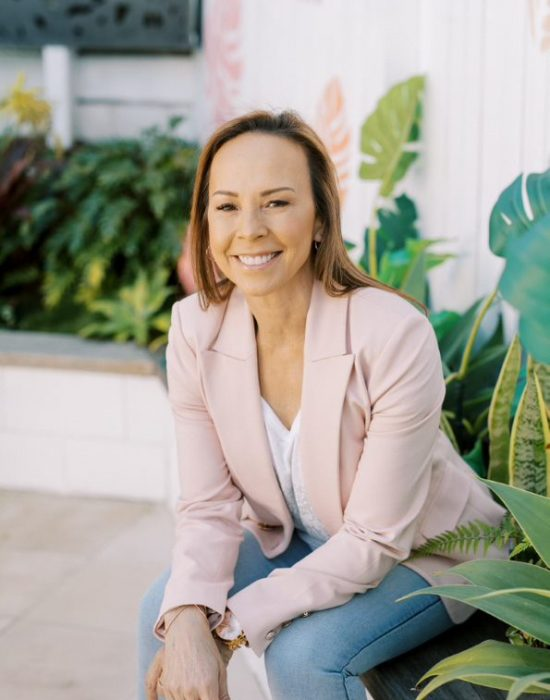 Hypnotherapy FAQs - Lai sitting on a bench surrounded by plants
